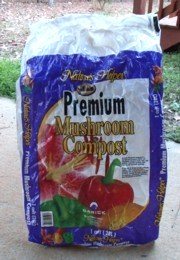 Mushroom compost is compost used to grow mushrooms in. After the mushroom harvest, the compost is sold.  Good stuff.
